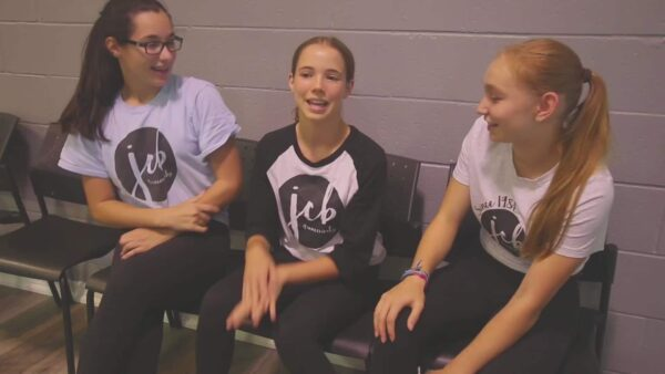 3 senior competitive dance students sitting in waiting area of dance studio near vaughan