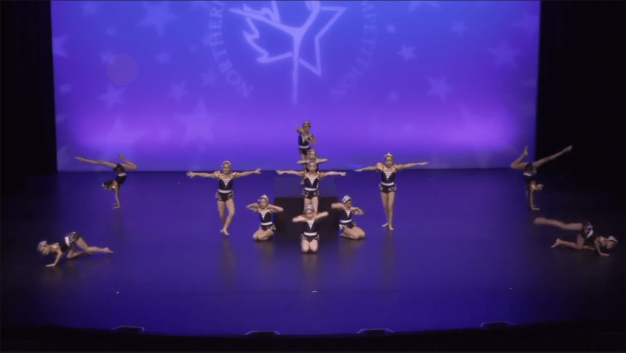 Competitive acro dancers on stage at dance competition in york region