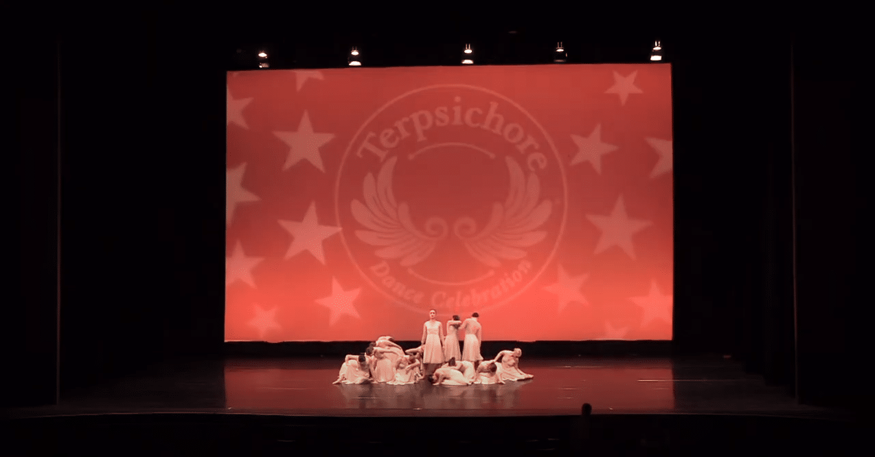 Competitive lyrical dancers on stage at dance competition in maple